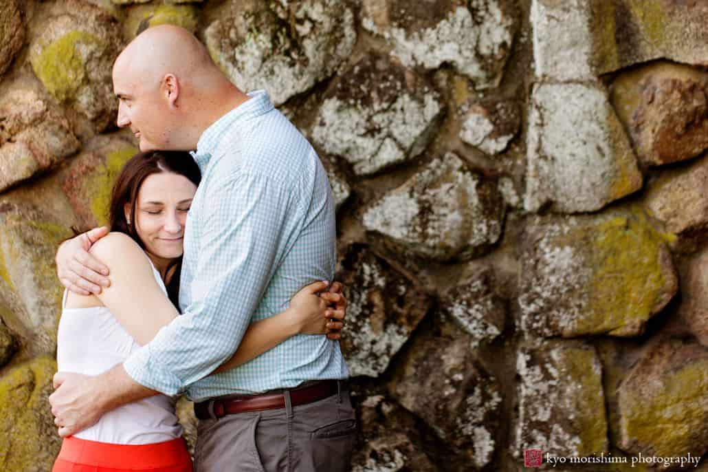 Couple hugs in front of mossy, stone wall in Hillsborough, NJ for engagement photo shoot. Woman wears red skirt and white blouse. Man wears light blue gingham shirt and grey pants. French chateau, European estate feel.