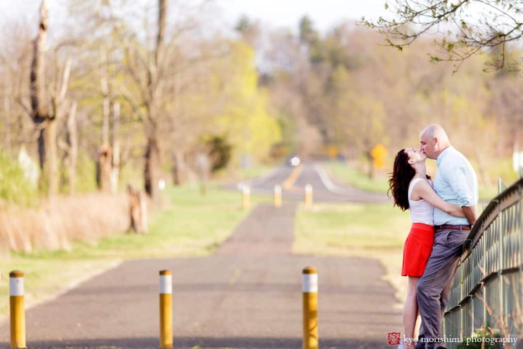 Couple kisses while leaning against bridge railing for Hillsborough, NY photographer. Spring engagement photo session. Long road and wooded background with hues of green, brown and yellow. Woman wears red skirt and white blouse while man wears blue gingham button down shirt and grey pants.