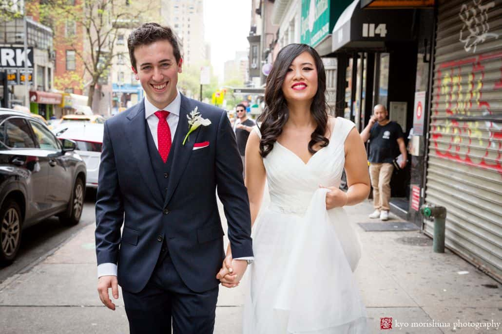 bride and groom smile and hold hands and walk down street in NYC, David's Bridal wedding dress, groom wears red tie and white boutonniere, NYC Spring wedding photogapher.