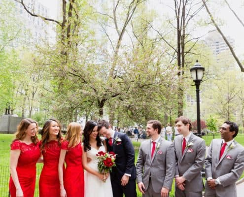 Groom leans head against bride surrounded by wedding party at madison square park wedding photo shoot NYC. red lace bridesmaid dresses from Lulu's, grey groomsmen suits with red ties, David's Bridal wedding dress, red and white wedding bouquet, Spring NYC wedding photos..