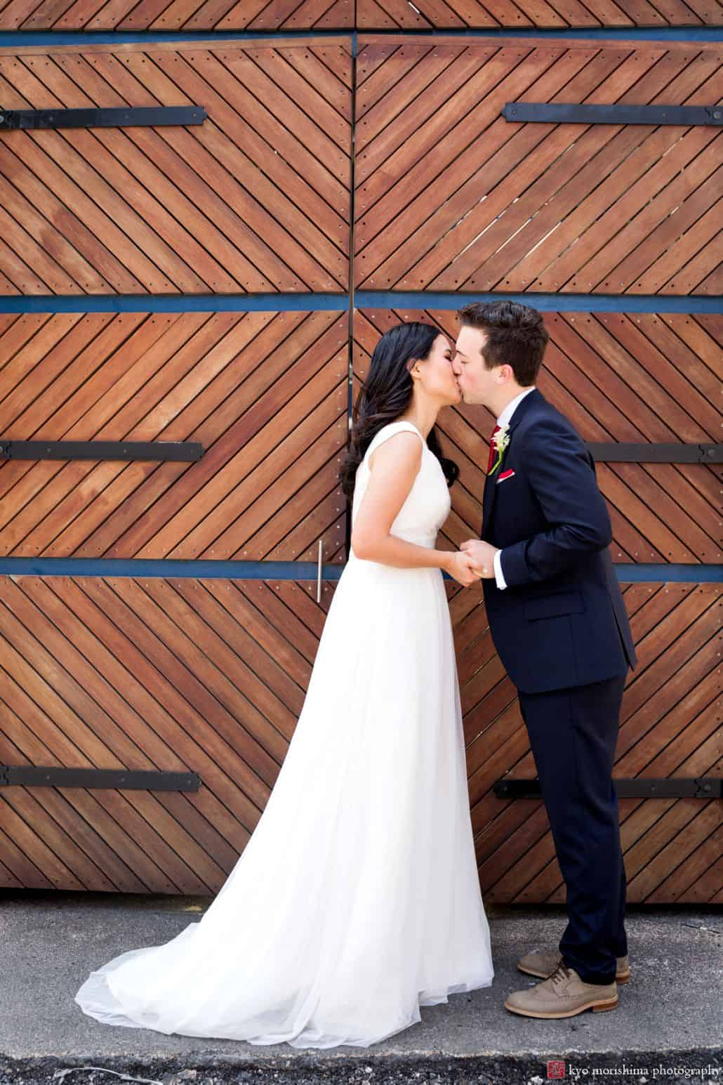 bride and groom kiss in front of large, chevron pattern wood and metal door. David's bridal wedding gown, Madison square park wedding photos NYC.