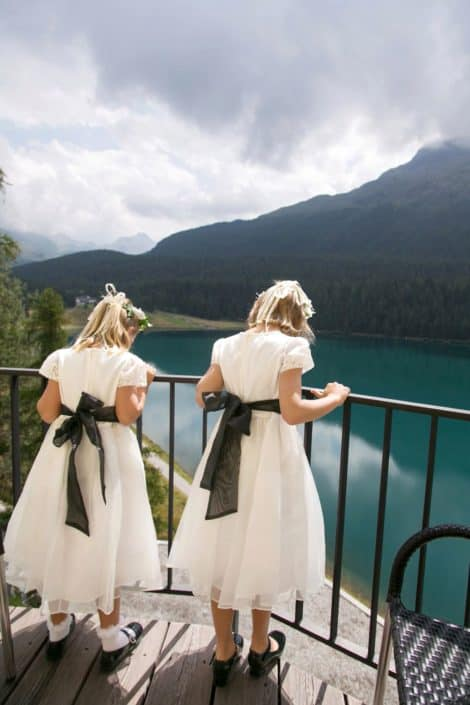 Flower girls in ivory dresses with black sashes lean on iron railing and overlook Lake St. Moritz at European destination wedding in Switzerland. Mountain and cloud background.