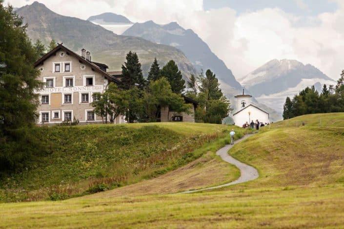 Hotel Sonne, Switzerland European destination wedding, winding road, grassy hills, Swiss Alps.