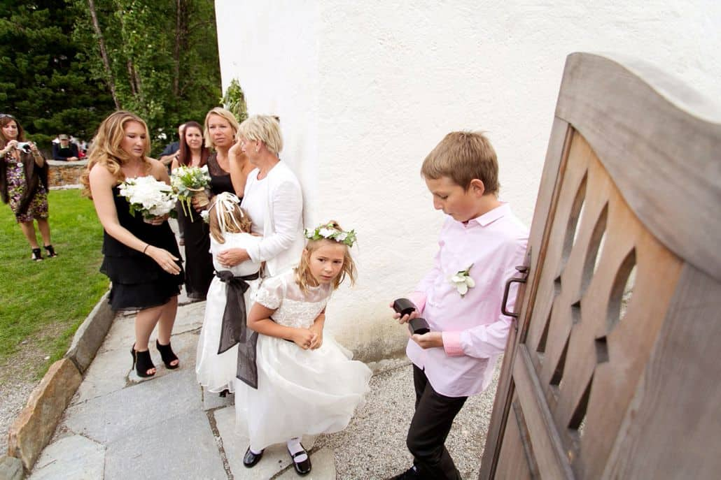 Flower girl and wedding party gathers along stone walkway inside carved wooden gate, European destination wedding photographer, Lake St. Moritz Switzerland, Waldhaus Hotel, Gardenias Floral.