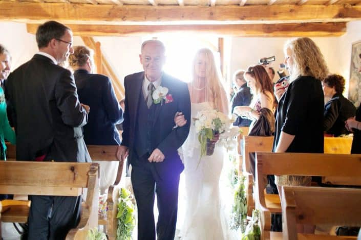 Bride walks down aisle with her father at tiny Romanesque church in the Swiss Alps. European destination wedding photographer, Swiss Alps. Gardenias Floral.