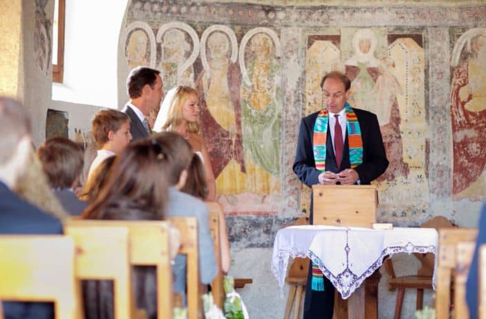 Bride and groom listen as officiant performs wedding ceremony at European destination wedding in a tiny Romanesque church in the Swiss Alps. Aged painted wall mural background.