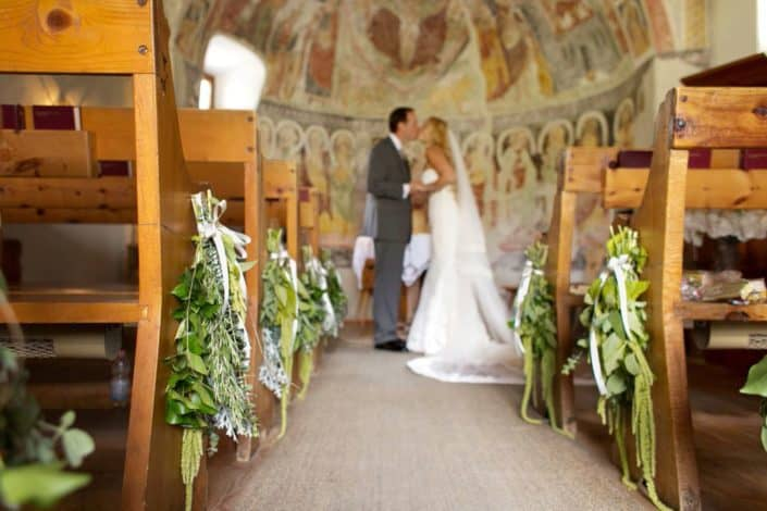 Bride and groom kiss at end of aisle in tiny Romanesque church at European destination wedding in Swiss Alps. Green and white bouquet pew arrangements, domed wall with aged, painted mural. Gardenias Floral.