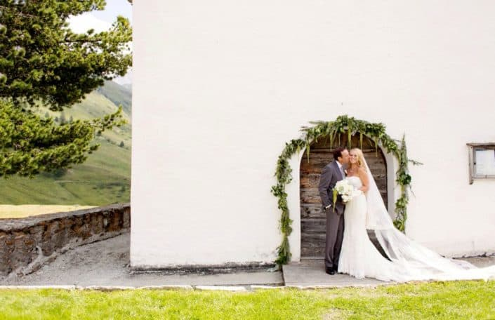 Groom kisses brides cheek in front of green floral covered archway on white wall at European destination wedding in Swiss Alps, destination wedding photography.