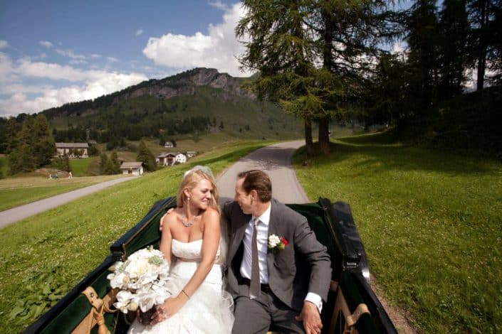 Bride and groom smile at each other in buggy ride at European destination wedding, white rustic wedding bouquet, strapless wedding dress with satin sash, Swiss Alps mountain background, winding road, small village.