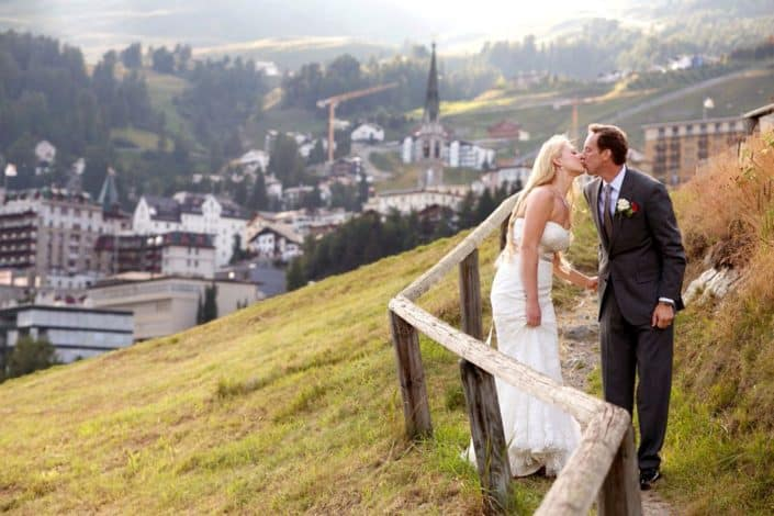 Bride and groom kiss next to old wooden fence on winding dirt path overlooking village in mountains, European destination wedding photography, Switzerland.