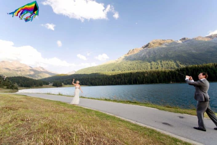 Bride and groom fly rainbow colored kite along path on Lake St. Moritz in Switzerland. Mountain and blue sky background. European destination wedding photographer,