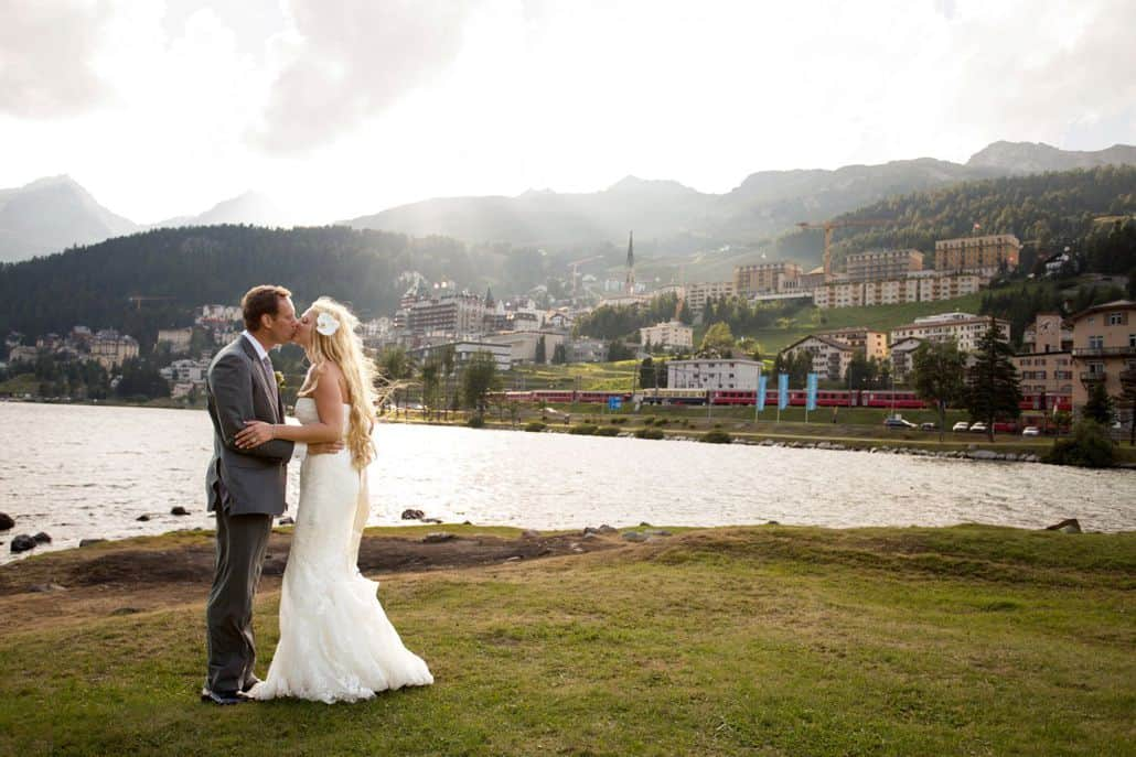 Bride and groom kiss in front of Lake St. Moritz in Switzerland, village along mountainside in background, white strapless wedding dress with satin sash, groom wears grey suit. European destination wedding photographer.