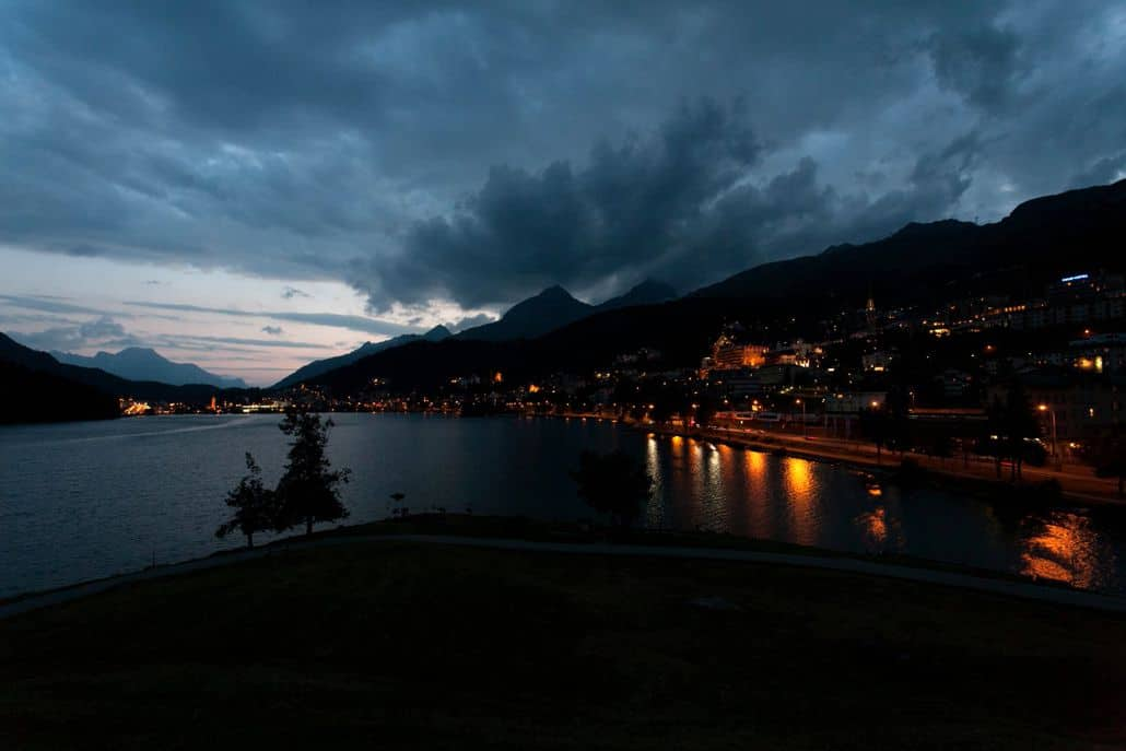 Night photography on Lake St. Moritz at European destination wedding in Switzerland, village on mountainside, cloudy skies, evening wedding photo.