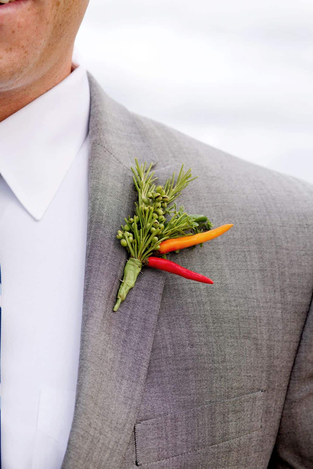 green foliage with red and orange pepper boutineer on gray suit, Dahlias Florist, Spring Lake NJ wedding photographer.