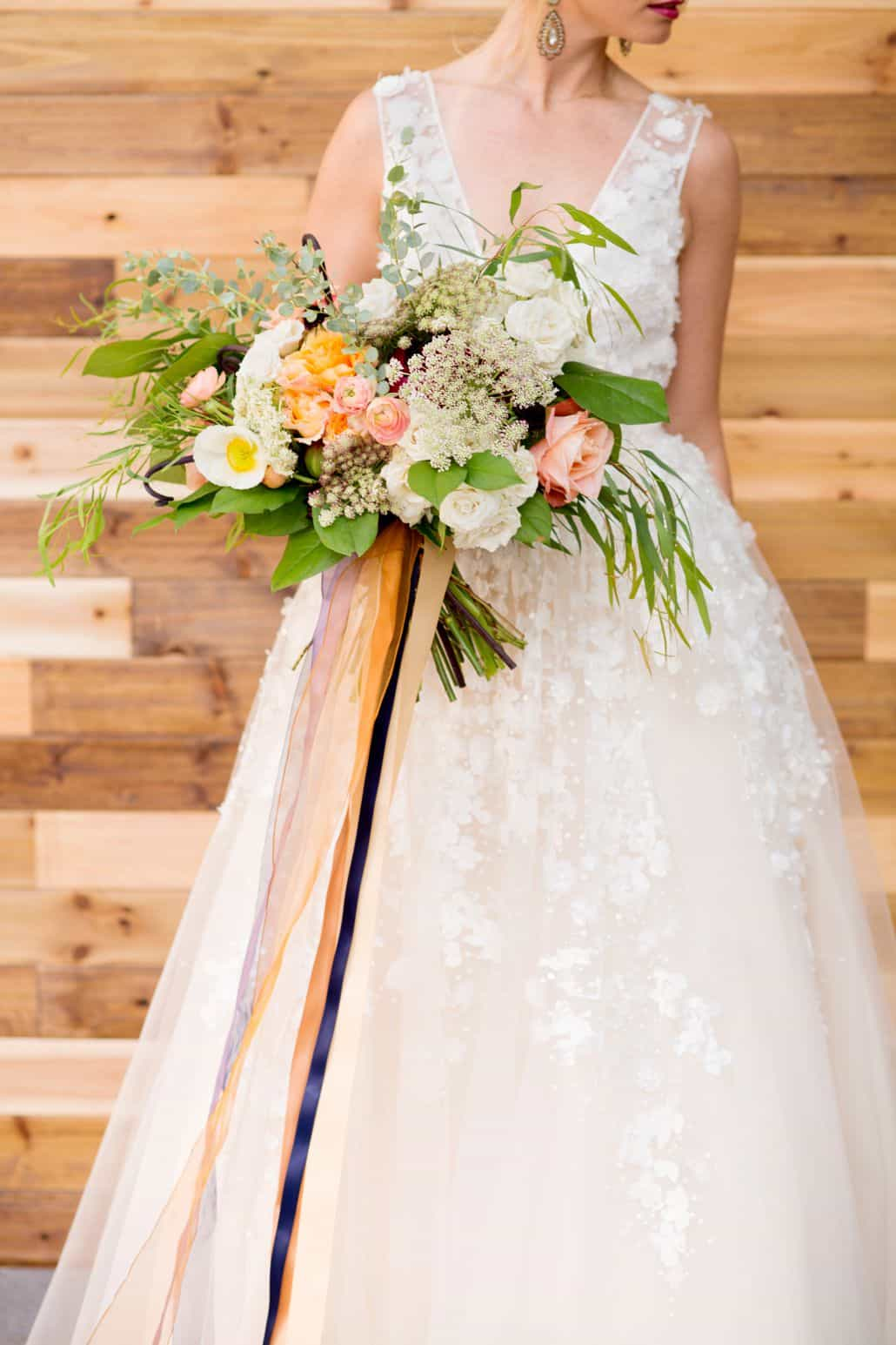 bride holds wildflower wedding bouquet, pink, orange, white, yellow ...