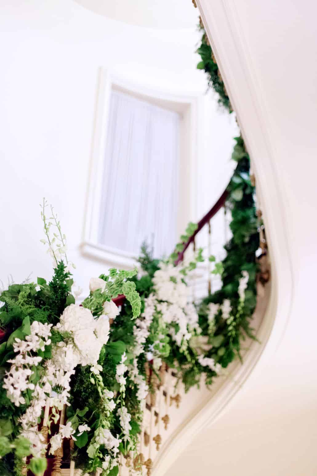 white and green floral arrangement up winding staircase railing ...