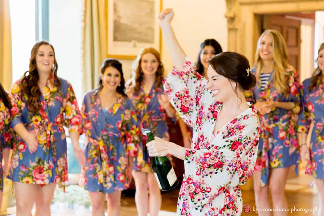 Bride in floral silk robe opens bottle of champaign while getting ready for her wedding. Bridesmaids in floras silk robes watch and smile. Jasna Polana wedding photographer. Spring new jersey wedding.