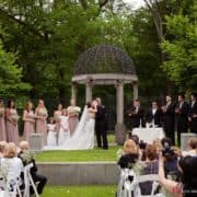 bride and groom kiss for first time as man and wife at non-denominational wedding ceremony at Jasna Polana under rounded top gazebo. Pronovias wedding gown. bridesmaids in greige Azazie dresses carrying baby's breath bouquets by Janet Mckrancy's wedding parties, groomsmen in Jos . A. Bank. suits. outdoor wedding ceremony. Jasna Polana wedding photographer.
