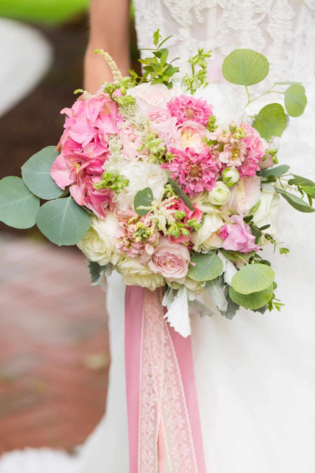 Bride In Lace Gown Holds Pink Cream And Green Wedding Bouquet