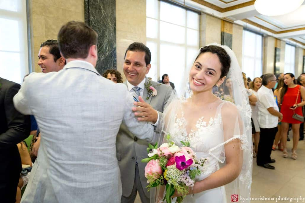 Nyc city hall elopement photographer a beautifully simple affair bride smiles at camera carrying pink fuschia and white bouquet while father congratulates groom at junglespirit Images