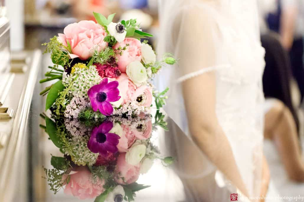 Pink, fuschia and white wedding bouquet lies on reflective surface with bride in background. Homecoming florist. NYC City Hall elopement photographer.
