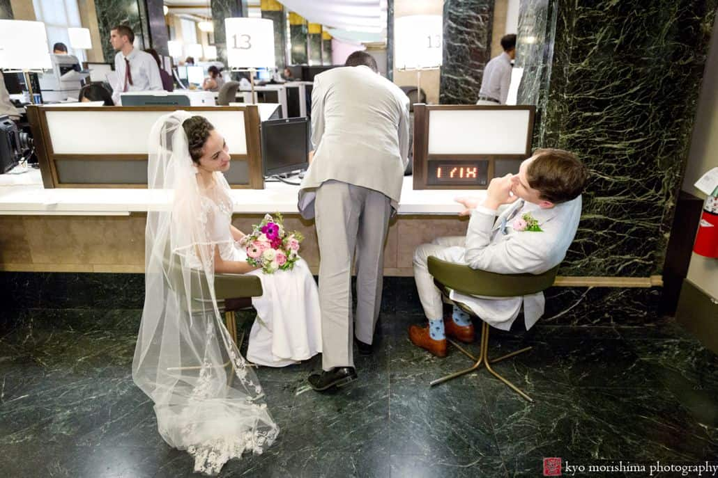 Bride and groom lean back in chairs to smile at one another as witness signs their wedding certificate during NYC City Hall wedding. Bouquet in bride's lap. Long veil pooled on floor. Summer NYC elopement wedding. Homecoming florist.