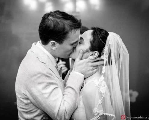 black and white photo of bride and groom's first kiss as man and wife. Bride's hair braided crown. NYC City Hall elopement photographer. Summer NYC wedding photo.