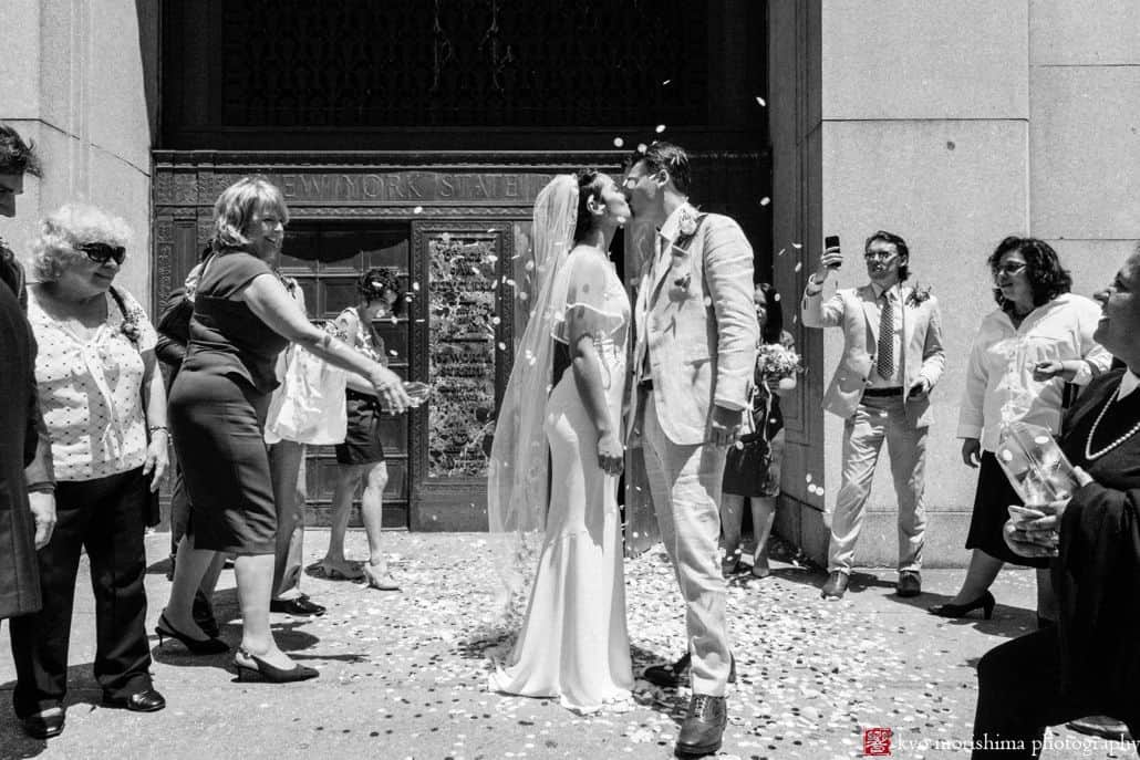bride and groom kiss outside City Hall as guests throw petals. NYC City Hall elopement photographer. Black and white wedding photography. Summer NYC wedding.