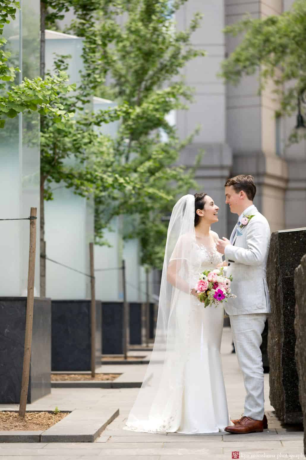 NYC City Hall wedding photos: Bride and groom smile at one another outside City Hall. Pink, fuschia and white bouquet, groom wears light gray linen suit. Small trees in the background. Summer NYC City Hall wedding photos. Homecoming florist.