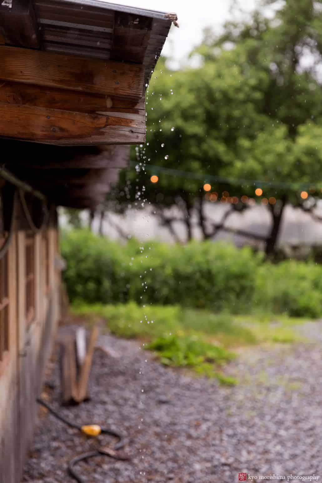 rain drops fall and splash from tin rooftop onto gravel path at Blooming Hill Farm wedding. New York wedding photographer. Rain wedding day photos.