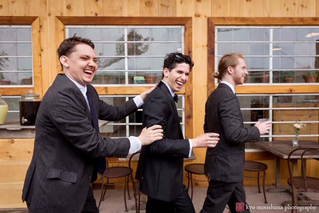 groomsmen laugh and walk with groom at Blooming Hill Farm wedding. Charcoal gray groomsmen suits. June NYC rainy day wedding. Blooming Hill Farm Wedding photographer.