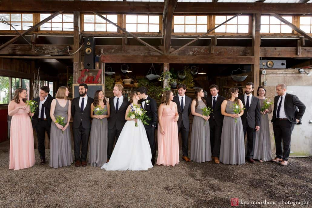 Bride and groom kiss surrounded by wedding party. Large wedding party. gray and peach bridesmaid dresses, charcoal gray groomsmen suits. Designer Loft wedding gown, Fleur di re wedding bouquets. Blooming Hill Farm wedding photographer.