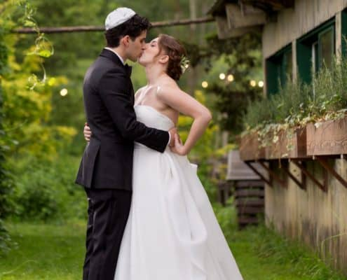 bride and groom kiss outside at Blooming Hill Farm wedding. Stone path, grass, greenery backdrop, rustic wooden window boxes, wooden branch archway, Designer Loft bridal gown, New York Jewish wedding photographer. Summer wedding. groom wears bow tie and kippah.