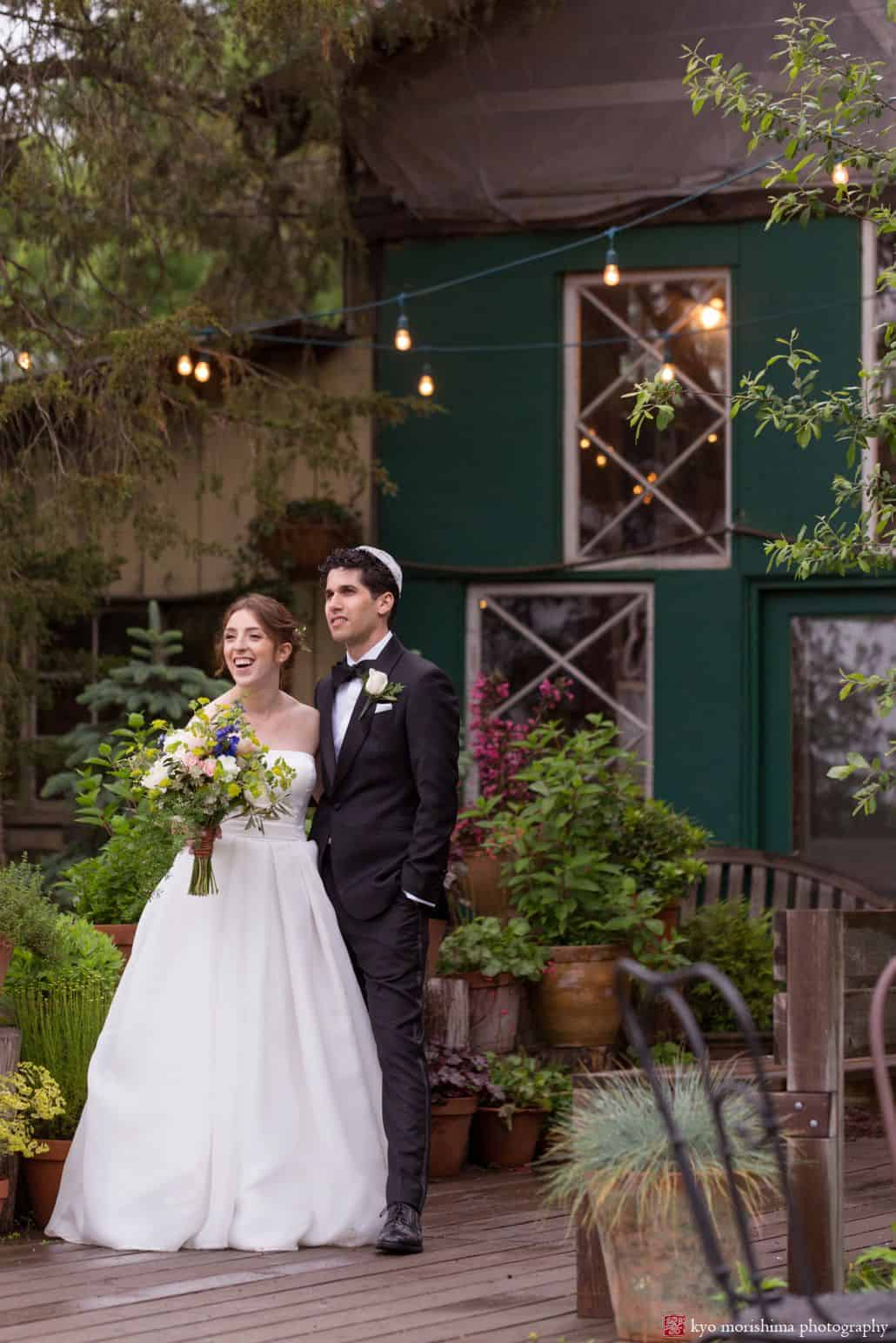 Bride and groom stand together and look on at Blooming Hill Farm wedding. Fleur di re bridal bouquet, Designer Loft wedding dress, green rustic cottage, greenery and potted plants on wooden deck, overhead string lights, NYC Jewish Summer wedding photographer. groom wears bow tie and kippah
