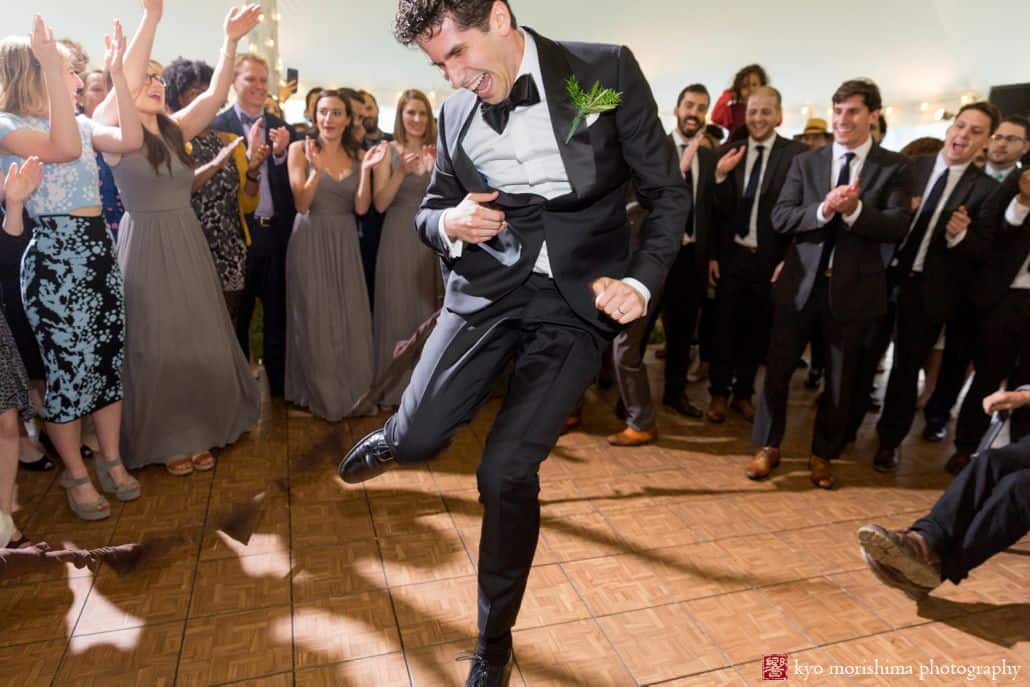 groom enthusiastically dances while guest form a circle around him at Blooming Hill Farm Jewish wedding. NYC June wedding photographer. Cartwright tent.
