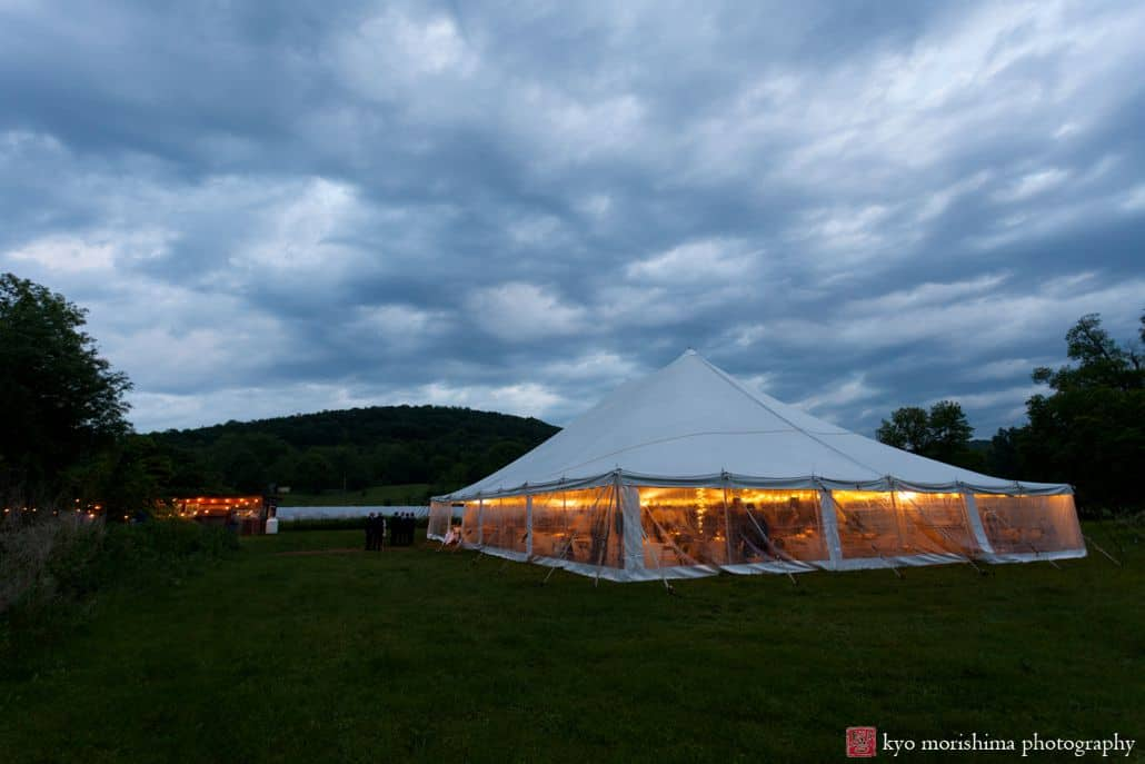 Cartwright wedding tent at dusk and cloudy skies at Blooming Hill Farm wedding. Background hills, foreground grassy turf, NYC Summer rainy day wedding photographer.