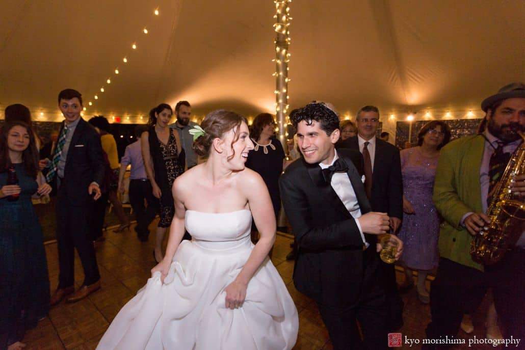 Bride and groom smile at each other and dance enthusiastically at Blooming Hill Farm wedding as west Philadelphia orchestra plays, Cartwright tent, Designer Loft bridal gown, Hudson Valley Ceremonies wedding planner, NYC Jewish wedding photographer. groom wears bow tie and kippah.