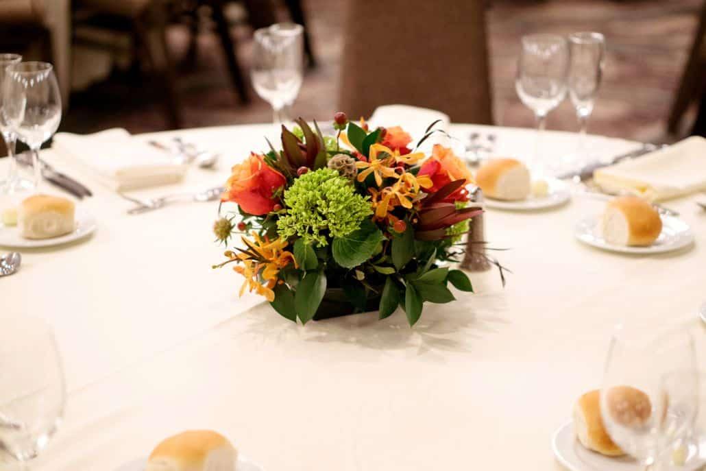 Burnt orange burgundy and green wedding table centerpiece