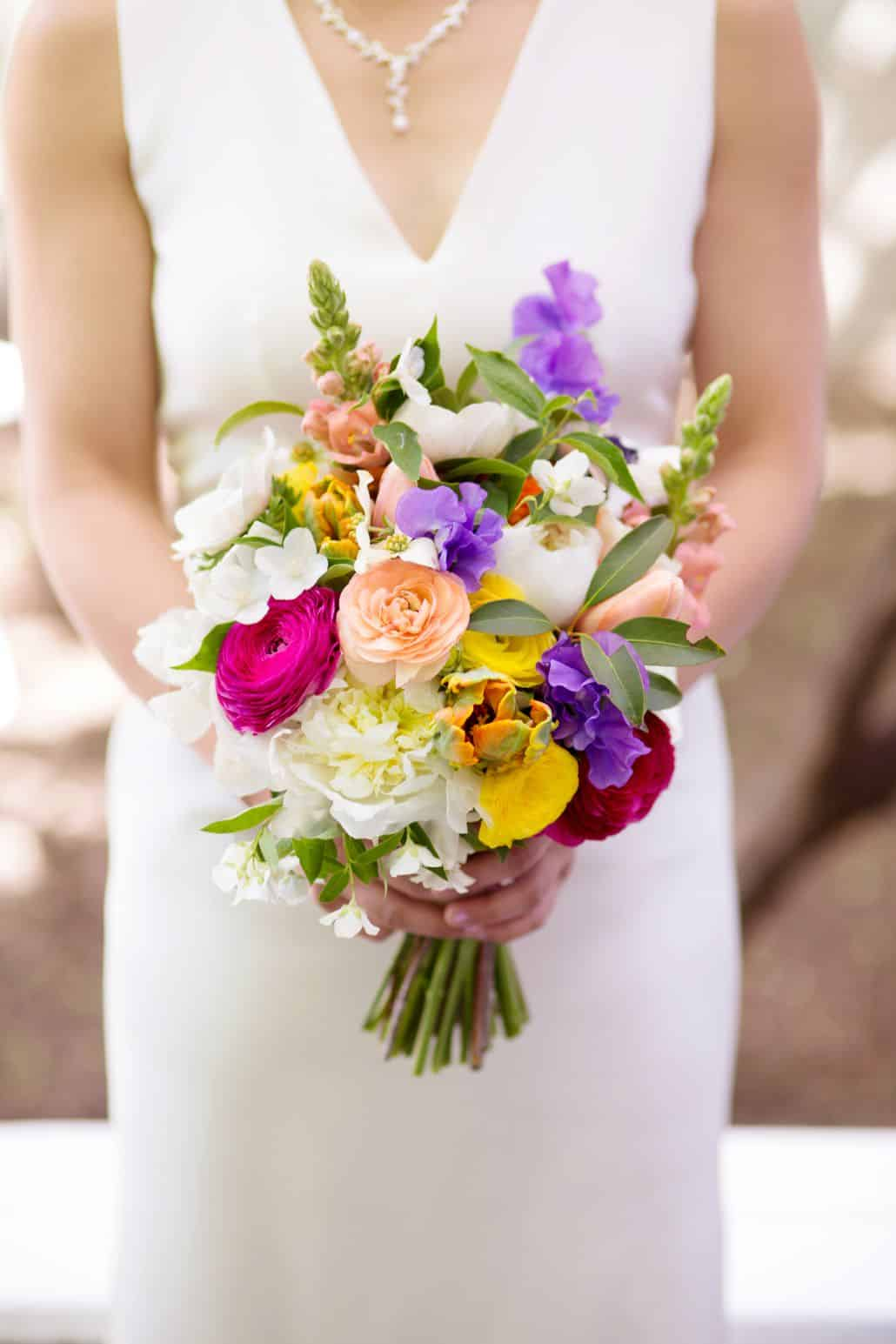 Bride Holds Colorful Mixed Bouquet Of Purple Pink Fuscia Yellow And White Flowers
