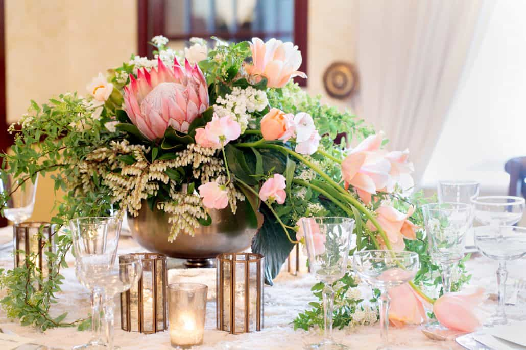 Wedding Table Centerpiece With Large Gold Urn Filled Pink And White Flowers Trailing Leaves