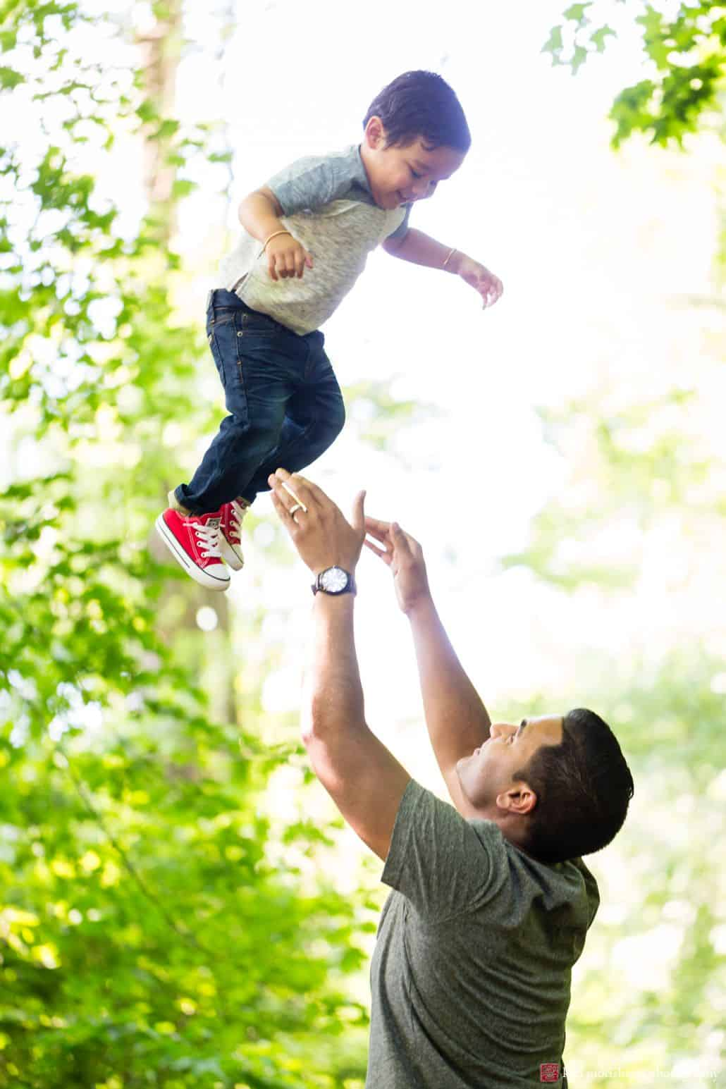 Documentary family photographer: father throws his son into the air during a springtime photo shoot in Princeton