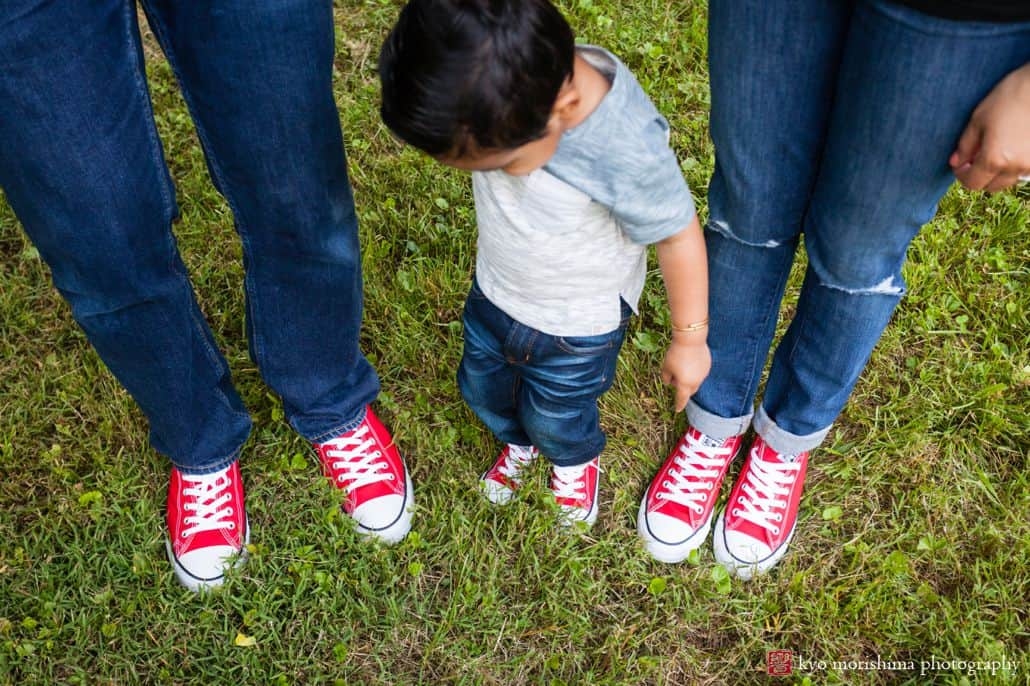 Family photojournalism: little boy looks down at his family's three pairs of red converse sneakers