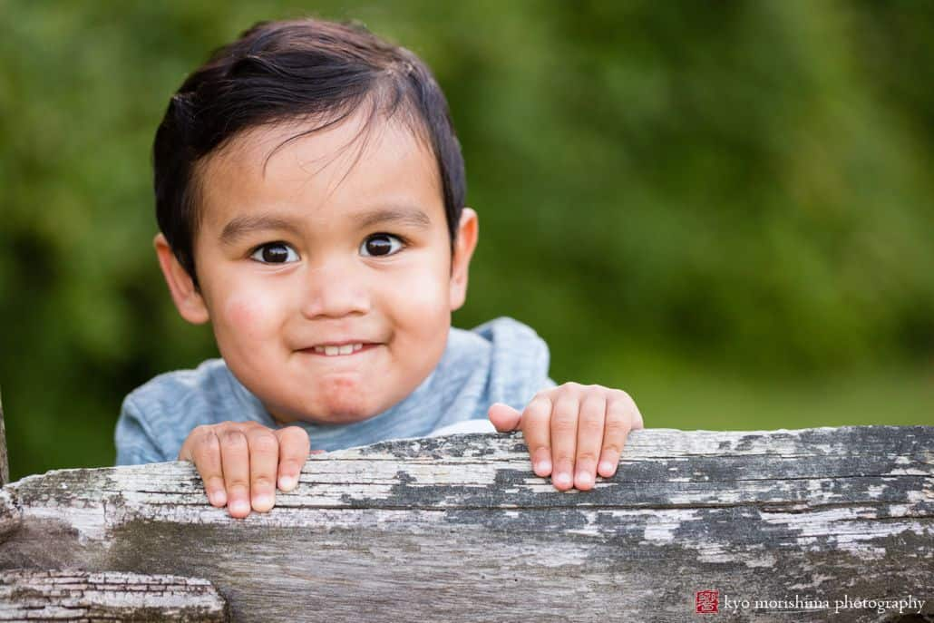 Portrait photographer in Princeton: young boy smiles as he stands on the edge of a wooden fence at Battlefield Park
