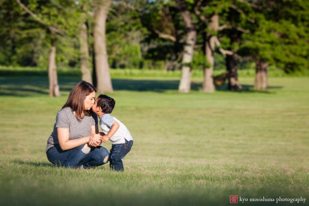 Documentary family photographer, NJ: little boy gives mom a kiss as they play in Battlefield Park