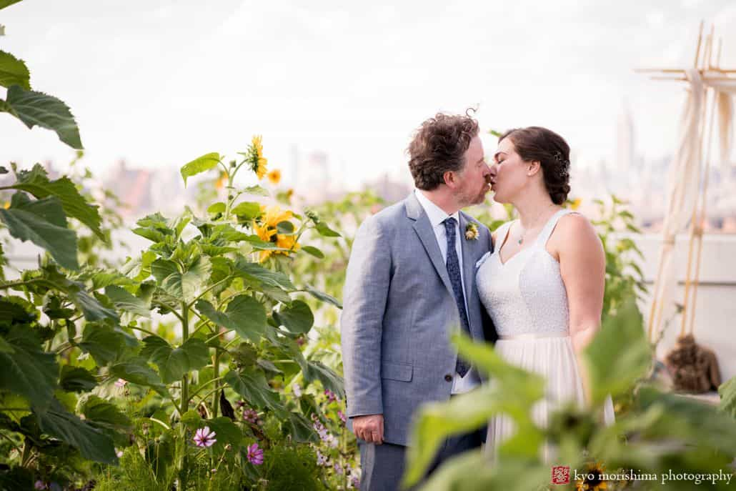 Brooklyn Grange wedding photos with sunflowers in the foreground as bride and groom kiss