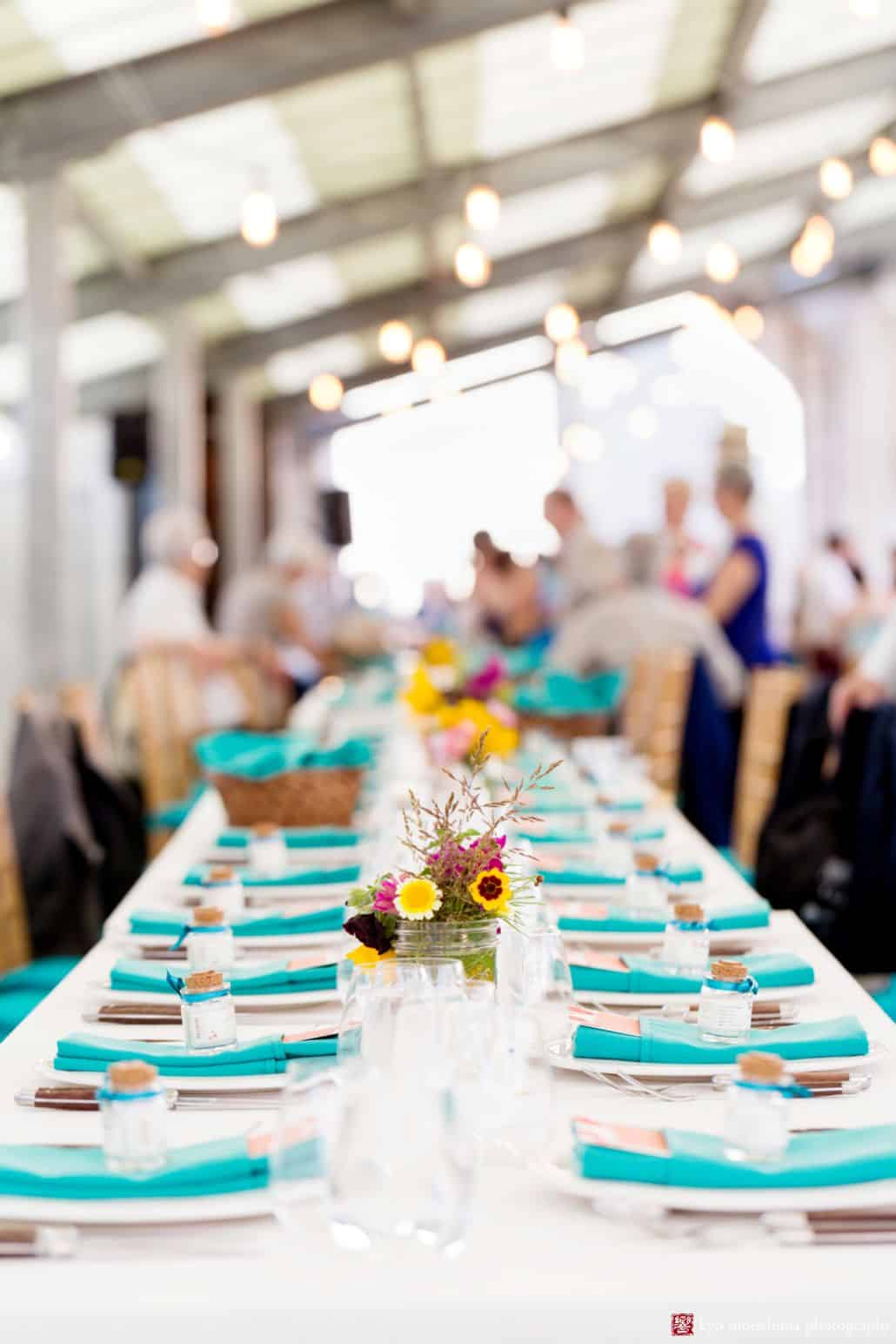 Party table with teal napkins and wildflowers at Brooklyn Grange summer wedding reception