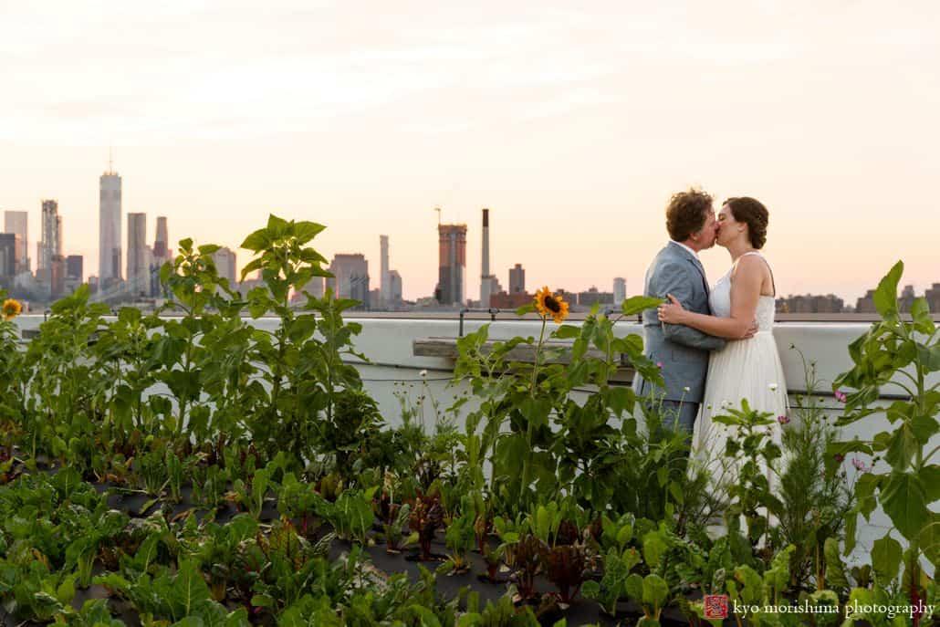 Bride and groom rooftop kiss during Brooklyn Grange wedding celebration in summer