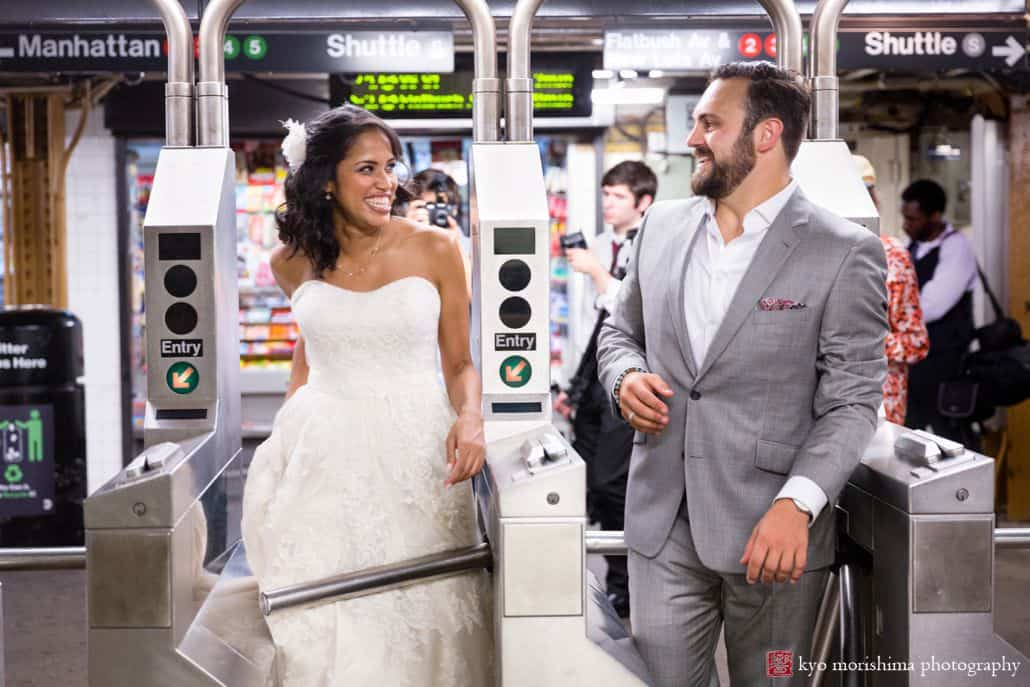 NYC subway wedding photo: bride and groom smile at each other as they walk through the MTA turnstile