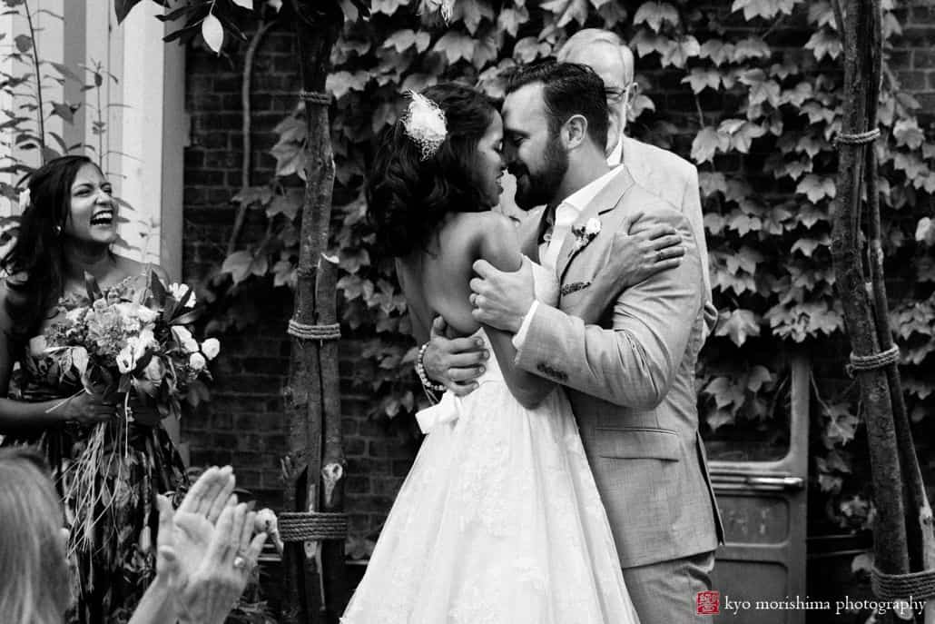 Brooklyn wedding photographer: candid shot of bride and groom at the end of their wedding ceremony at Electric Anvil Tattoo in Crown HeightsBrooklyn wedding photographer: candid shot of bride and groom at the end of their wedding ceremony at Electric Anvil Tattoo in Crown Heights