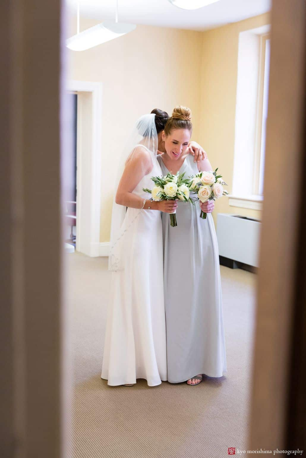 Bride and bridesmaid hug before wedding ceremony at Hunterdon County courthouse. BHLDN bridal gown, The Pod Shop flowers, New Hope, intimate wedding, PA wedding photographer.